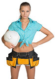 Pretty girl in shorts, shirt and tool belt holding white helmet