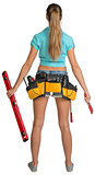 Pretty girl in shorts, shirt and tool belt with tools. Full length rear view