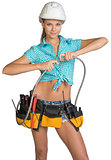 Pretty girl in helmet, shorts, shirt and tool belt with tools connects two flexible hose for plumbing