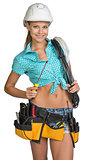 Pretty electrician in helmet, shorts, shirt, tool belt with tools holding screwdriver and an electric cable