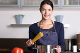 Young housewife preparing a healthy Italian pasta