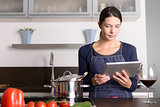 Young woman looking at a recipe on her tablet
