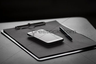 Smartphone, clipboard and pen
