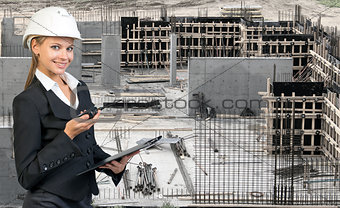 Beautiful businesswoman in helmet holding paper holder and portable radio. Construction site as backdrop