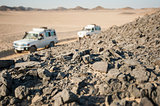 Vehicles driving through rocky desert