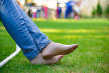 Woman Barefoot Legs on the Green Grass in Garden
