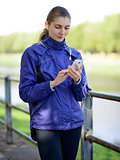 Young Beautiful Sports Woman Using her Phone in the Park