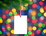Christmas Greeting Card on the Fir Branch on the Holiday Lights Background