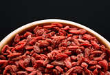 Wooden Bowl Full of Dried Goji Berries on the Black Table