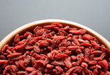 Wooden Bowl Full of Dried Goji Berries on the Dark Table