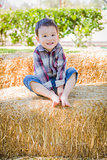 Cute Young Mixed Race Boy Having Fun on Hay Bale