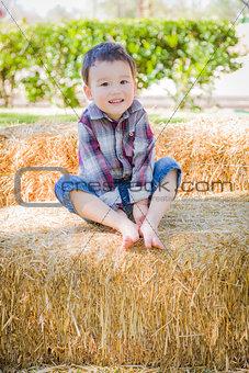 Cute Young Mixed Race Boy Having Fun on Hay Bale