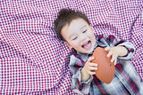 Young Mixed Race Boy Playing with Football on Picnic Blanket