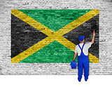 House painter covers brick wall with flag of Jamaica