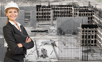 Beautiful businesswoman in helmet standing with crossed arms. Construction site as backdrop