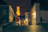 Cityscape with a picturesque night street and tower Belfort in Bruges