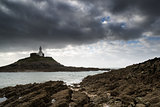 Lighthouse landscape with stormy sky over sea with rocks in fore