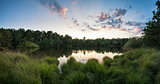 Summer sunset panorama landscape reflected in calm lake