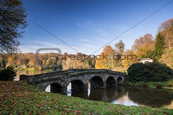 Bridge over main lake in Stourhead Gardens during Autumn.