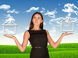 Businesswoman holding two houses as if chosing