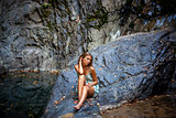 beautiful girl posing in dress at the waterfall