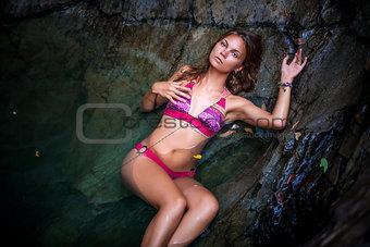Beautiful sexy model posing in water of waterfalls wearing bikini swimwear at summer time