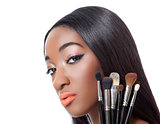 Black woman with straight hair holding makeup brushes
