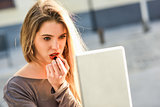 Young woman applying lipstick looking at tablet