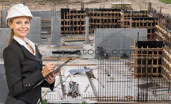 Beautiful businesswoman in helmet holding paper holder and writing. Construction site as backdrop