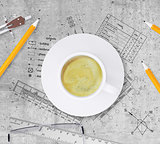Technical plan of building, pencils, ruler, compasses, eyeglasses and coffee cup