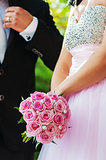 wedding bouquet of pink roses in hands of the bride