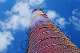 Industrial brick chimney against cloudy sky