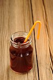 Cherry juice in jar with cocktail tube and vanilla vertical
