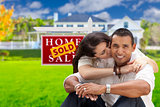 Hispanic Couple, New Home and Sold Real Estate Sign