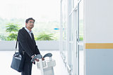 Indian businessman with airport trolley