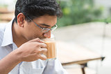 Indian businessman sipping a cup hot milk tea