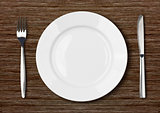 white empty dinner plate setting on dark wooden table