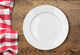 white empty dinner plate setting on wooden table with tablecloth