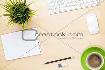 Office table with notepad, computer, coffee cup and flower