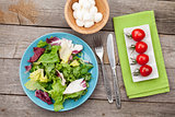 Fresh healthy salad, tomatoes, mozzarella on wooden table