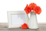 Orange gerbera flowers and photo frame on wooden table