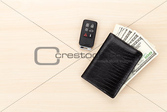 Money cash wallet and car remote key on wooden table