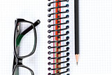 Office table with glasses, blank notepad and pencil