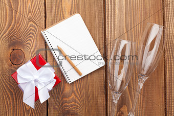 Blank notepad, valentines day gift box and two champagne glasses