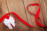 Heart shape ribbon and gift box over wood valentines day background
