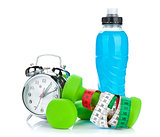 Two green dumbells, tape measure, drink bottle and alarm clock