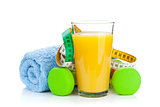 Two green dumbells, tape measure and orange juice