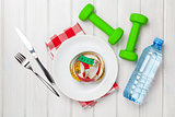 Dumbells and healthy food over wooden background