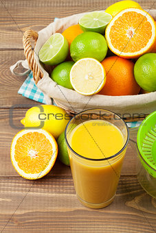 Citrus fruits in basket and glass of juice. Oranges, limes and lemons
