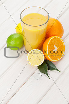 Citrus fruits and glass of juice. Oranges, limes and lemons